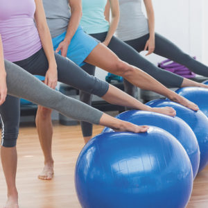 Fysio-pilates, 5 klienter laver fysio-pilates med en stor terapibold