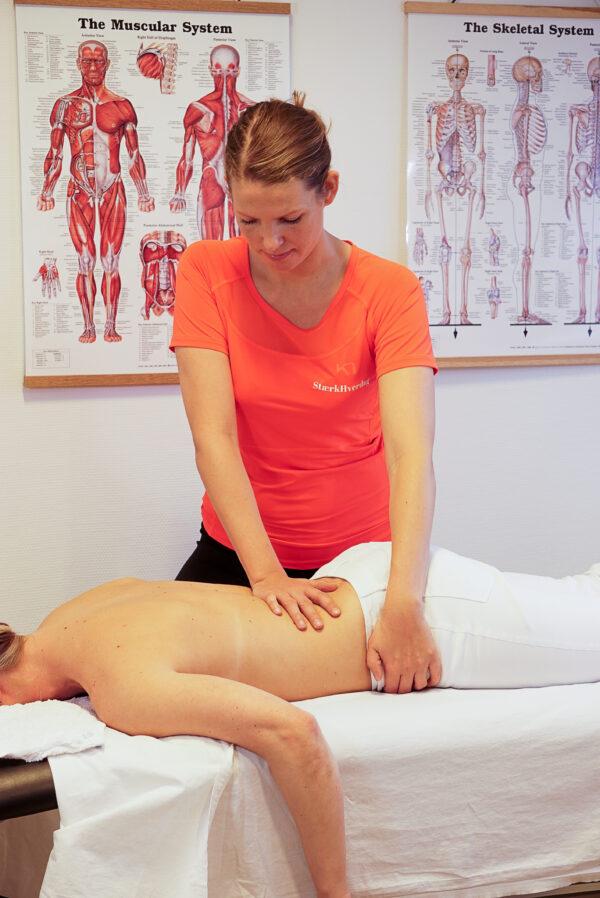 Fysioterapeut behandler kvinde med ondt i lænden