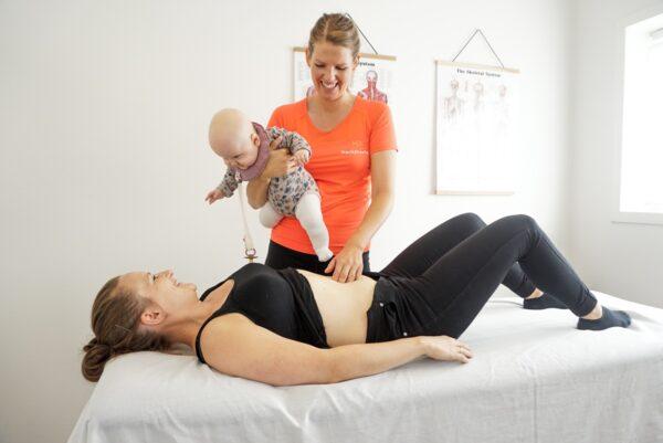Fysioterapeut-tjekker-delte-mavemuskler-med-baby-på-armen